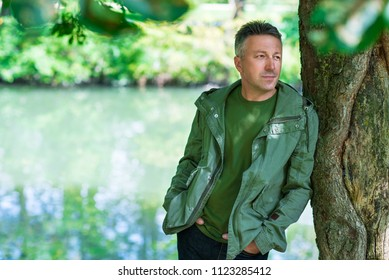 Handsome middle-aged man posing and looking at camera in autumn park over foliage and river. Outdoor male portrait.