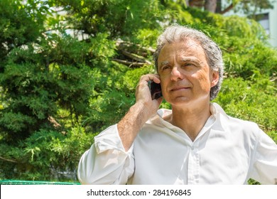 Handsome middle-aged man with salt pepper hair dressed with white shirt is talking on mobile phone in city park: he shows a reassuring look
