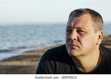 Handsome middle-aged man sitting thinking in the sunlight at the coast with a serious expression and ocean backdrop