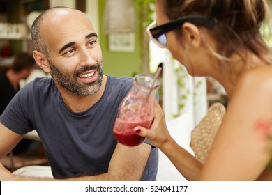 Handsome middle-aged man with stubble sitting at sidewalk restaurant, having nice conversation with attractive female who is drinking smoothie. Two tourists talking over lunch at cafe during holidays
