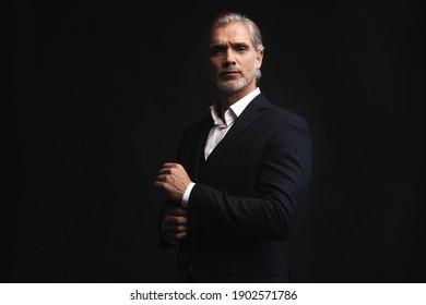 Handsome Mann mittleren Alters in Anzug, der schwarzer Hintergrund