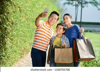Handsome middle-aged man taking selfie with his pretty wife and little son after successful completion of shopping day, picturesque view on green public park on background
