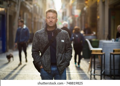 Handsome middle-aged man walking autumn street. Urban male portrait, image toned and noise added, soft focus.