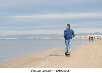 Handsome middle-aged man walking at the beach, back view.  Full-length outdoor portrait of beautiful macho man.