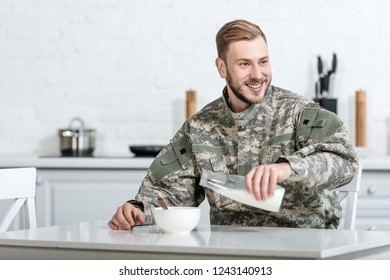 Handsome military man pouring milk in bowl with cornflakes in morning