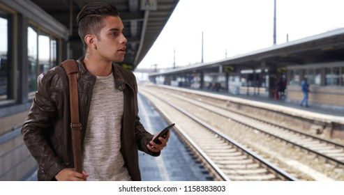 Handsome millennial Latin male at the train station hailing a ride