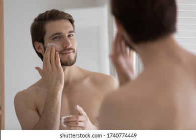 Handsome millennial man look in bathroom mirror after shower apply nourishing facial cream or mask, young caucasian male use moisturizing face balm for healthy glowing skin, skincare concept
