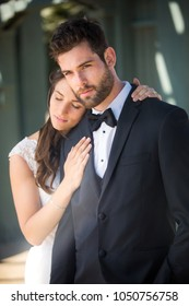 Handsome model groom standing strong next to newlywed wife in dramatic artistic pose portrait