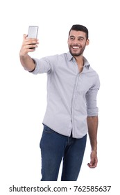 Handsome model wearing shirt and jeans is taking selfie. Isolatedl on white background.