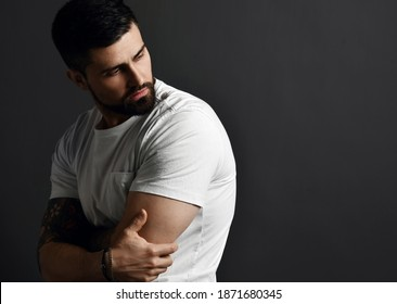 Handsome modern brutal bearded muscular man in t-shirt and with tattoo on arms stands side to camera looking back at copy space over grey background. Hipster stylish look for free lifestyle concept