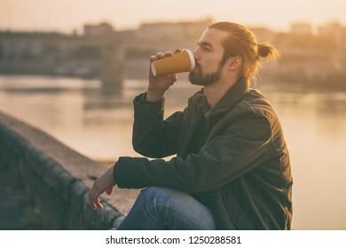 Handsome modern businessman enjoys drinking coffee and resting by the river.Toned image.