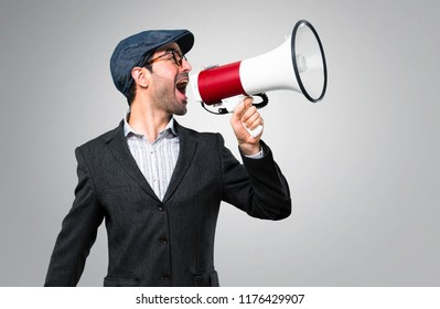 Handsome modern man with beret and glasses holding a megaphone on grey background