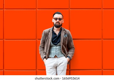 Handsome, modern man, in casual style on a background of lush lava color wall, trend, urban mood.