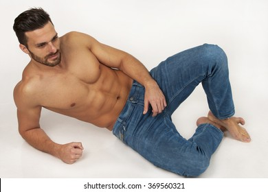 Handsome modern strong muscular man in blue jeans laying on white background in studio, with beard, bare foot