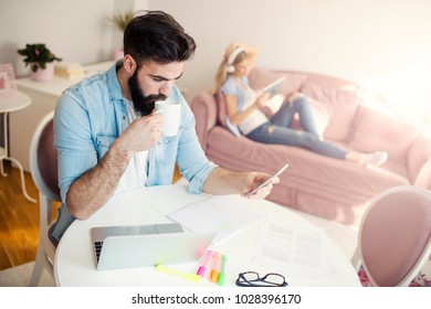 Handsome modern young freelancer using phone and drinking coffee
