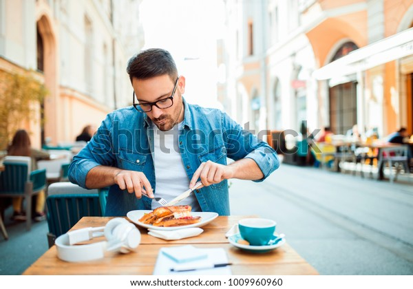 Handsome modern young man eating breakfast at cafe