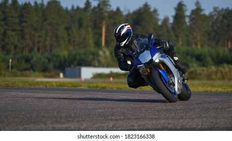 Handsome motorcyclist in black riding his super sport motorcycle