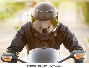 Handsome motorcyclist in black riding his super sport motorcycle. Soft focus. Lens flare