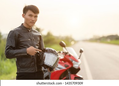 Handsome motorcyclist wear leather jacket and holding helmet on the road. Safe ride and transportation concept