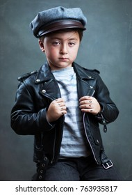 Handsome multi-racial Asian Caucasian little biker boy wearing a black leather motorcycle jacket and a gray pilots cap hat with tattoos on his hands that say Love and Hate