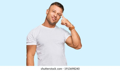 Handsome muscle man wearing casual white tshirt smiling pointing to head with one finger, great idea or thought, good memory