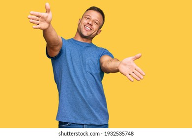 Handsome muscle man wearing casual clothes looking at the camera smiling with open arms for hug. cheerful expression embracing happiness.