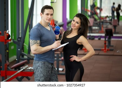 Handsome muscled male trainer consulting attractive young female in gym, both smiling