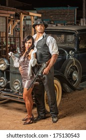 Handsome muscular 1920s gangster with lady in mini skirt