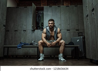 handsome muscular athletic man with a towel in the locker room after working out