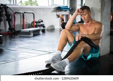 handsome Muscular bodybuilder guy with sitting with battle ropes relax after exercise in fitness gym . Tired Shirtless young sport man resting after training with sweat . worry,sad,strain,copy space