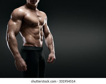 Handsome muscular bodybuilder posing over black background. Isolated with clipping path.