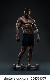 Handsome muscular bodybuilder preparing for fitness training. Pumping up muscles with dumbbells. Studio shot on black background.