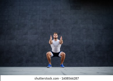 Handsome muscular caucasian man in shorts and t-shirt doing squatting exercise outdoors. In background is gray wall.