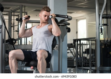 Handsome Muscular Fitness Bodybuilder In Undershirt Doing Heavy Weight Exercise For Biceps On Machine With Cable In The Gym