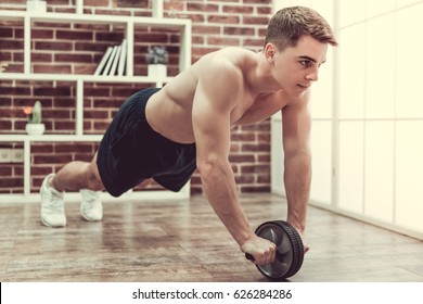 Handsome muscular guy with bare torso is working out with exercise wheel at home