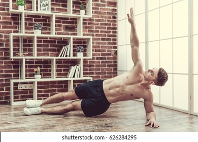 Handsome muscular guy with bare torso is doing side plank exercise while working out at home