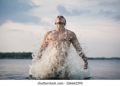 Handsome muscular guy jumping from water