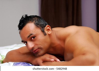 Handsome muscular hispanic male model lying on a bed