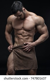 Handsome muscular male in front of black background