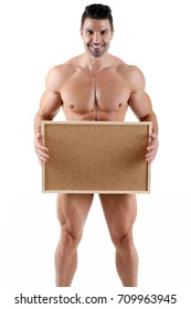 Handsome muscular male holding empty corkboard in front of white background
