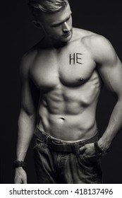 """Handsome muscular male model with intense glance posing over grey background. Perfect body with the inscription """"he"""" on his chest . Studio shot"""