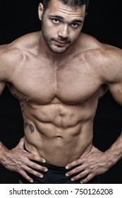 Handsome muscular male portrait, isolated on black background