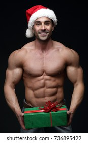 Handsome muscular male with Santa hat holding Christmas gift, isolated on black background