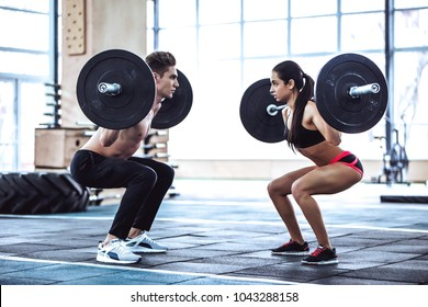 Handsome muscular man and attractive sporty woman are working out in gym. Couple making cross fit training. Squatting with barbells together