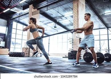 Handsome muscular man and attractive sporty woman are working out in gym. Couple making cross fit training.