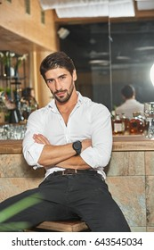 Handsome muscular man with a beard wearing white shirt and black trousers sitting in a bar with crossed arms, going to have a dinner in a restaurant.
