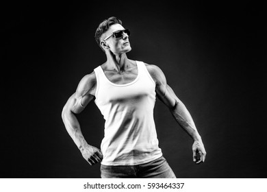 Handsome muscular man in dark glasses and a white shirt.