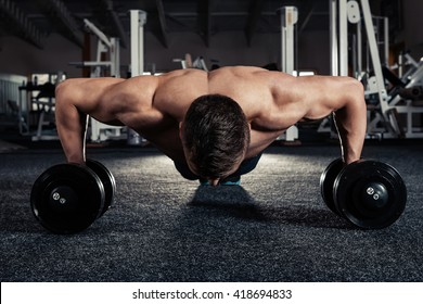 Handsome muscular man doing pushup exercise with dumbbell in a crossfit workout