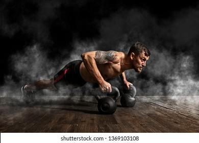 Handsome muscular man doing pushups on kettleball in gym - Image