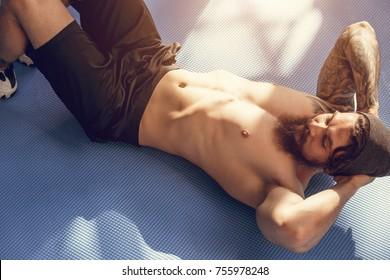 Handsome muscular man doing sit-ups on gym floor